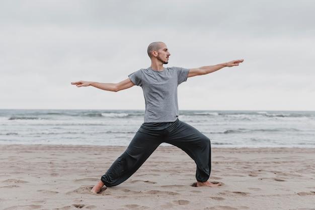 Вид сбоку человека, практикующего позы йоги на открытом воздухе