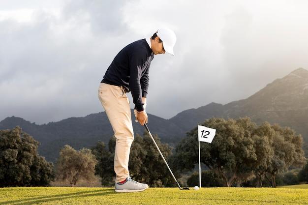 필드에 골프 공을 칠 준비 남자의 측면보기