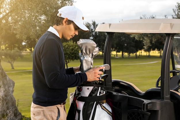 クラブをゴルフカートに入れる男の側面図