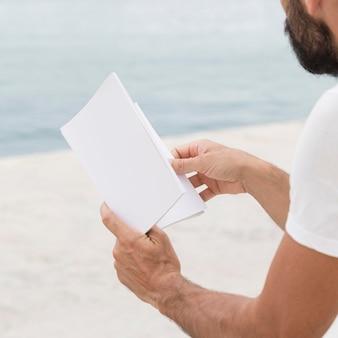 屋外で本を読んでいる男の側面図