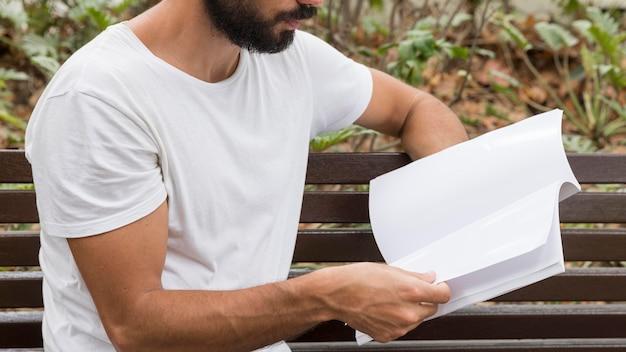 ベンチで本を読んでいる男の側面図