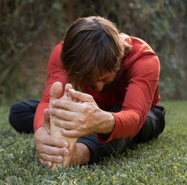 Вид сбоку человека, растягивающегося на траве на открытом воздухе во время занятий йогой