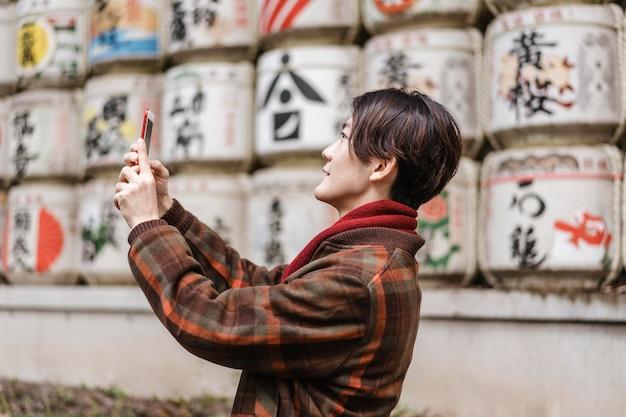 Вид сбоку человека, фотографирующего со своим смартфоном