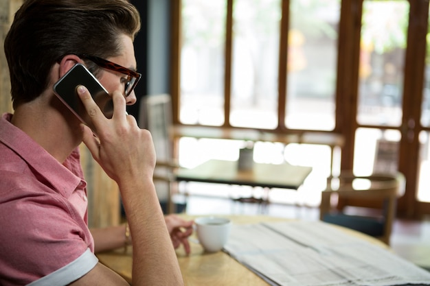 커피 숍에서 휴대 전화 통화하는 사람의 측면보기