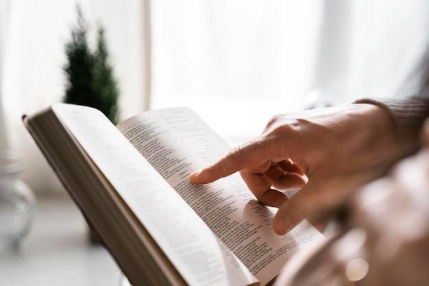 성경에서 읽기 위해 손가락을 사용하는 사람의 측면보기