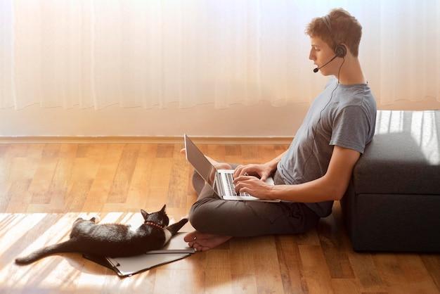 격리 된 집에서 노트북을 사용하는 사람의 측면보기