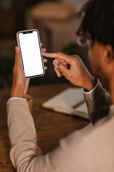 Вид сбоку человека, использующего современный смартфон дома