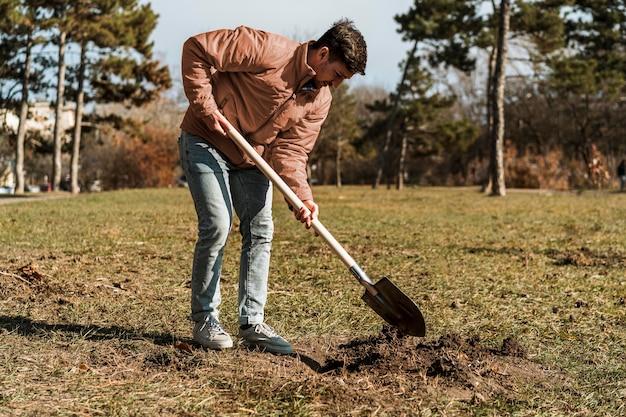 나무 심기 위해 구멍을 파기 위해 삽을 사용하는 사람의 측면보기