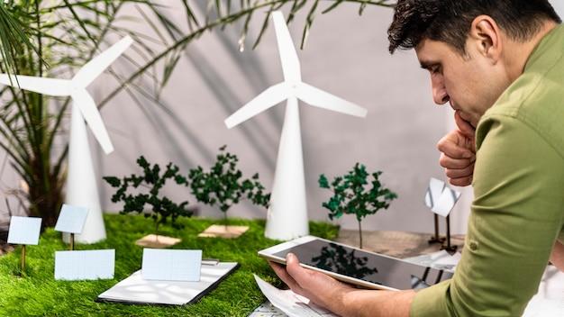 Вид сбоку человека, использующего планшет рядом с экологичным макетом проекта ветроэнергетики