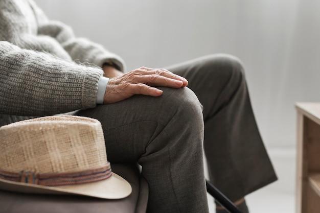 요양원에서 그의 모자를 가진 남자의 측면보기