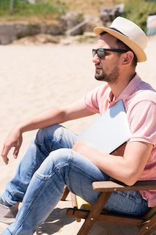ビーチでラップトップを持つ男の側面図