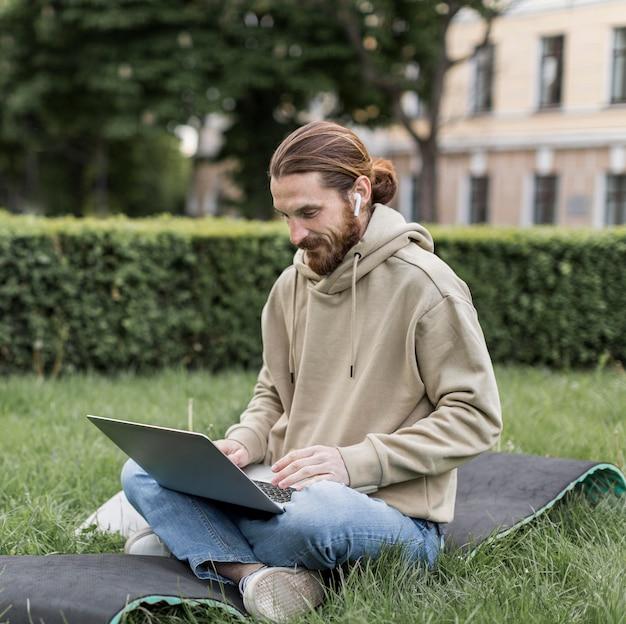 都市公園におけるラップトップを持つ男の側面図