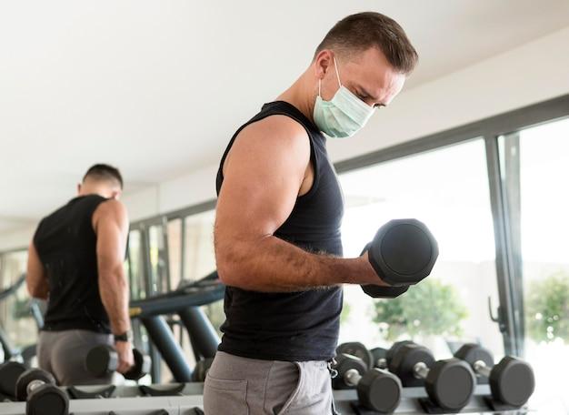 체육관에서 운동하는 의료 마스크를 가진 남자의 측면보기