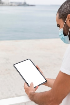 Вид сбоку человека с медицинской маской, держащего планшет на открытом воздухе