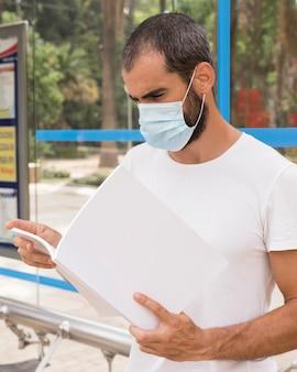 屋外で読書医療マスクを持つ男の側面図
