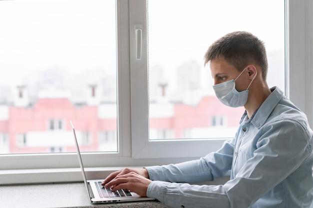 Вид сбоку человека с медицинской маской, работающего на ноутбуке