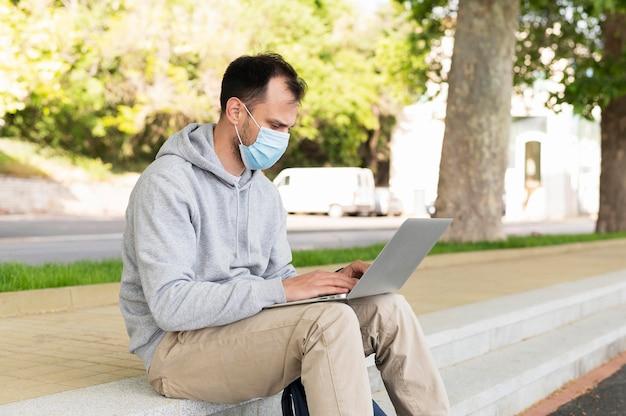 ラップトップで外で働く医療マスクを持つ男の側面図