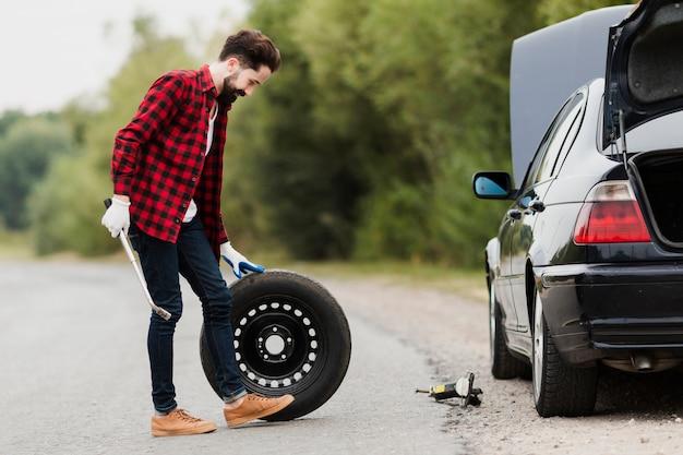 スペアタイヤを持つ男の側面図