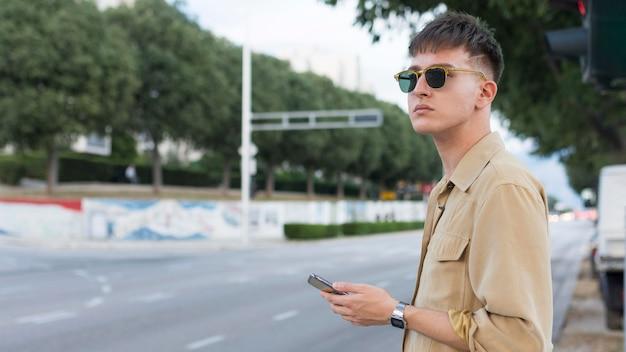 Вид сбоку человека в солнцезащитных очках в городе, держащего смартфон