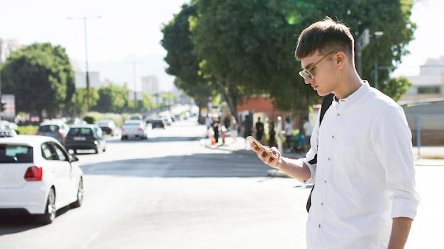 Вид сбоку человека в темных очках, смотрящего на телефон в городе