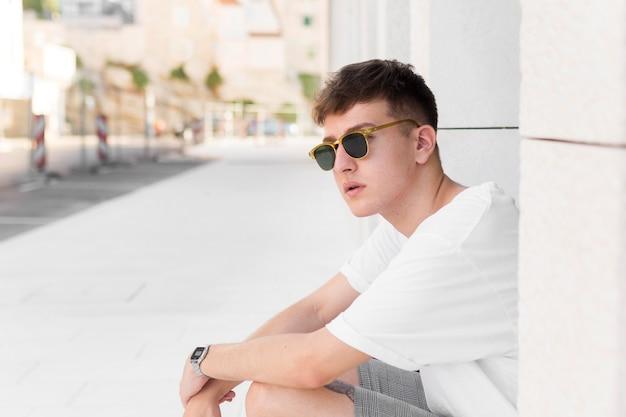 Вид сбоку человека в солнцезащитных очках, позирующем на открытом воздухе в городе