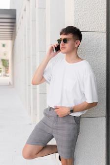 Вид сбоку человека в солнцезащитных очках, разговаривающего по телефону на открытом воздухе