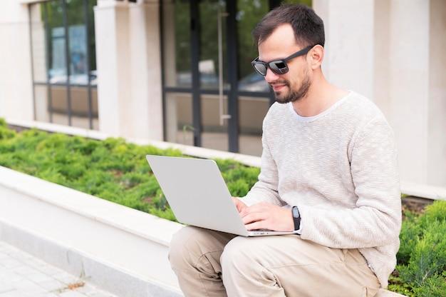 屋外のラップトップに取り組んでいるサングラスを持つ男の側面図