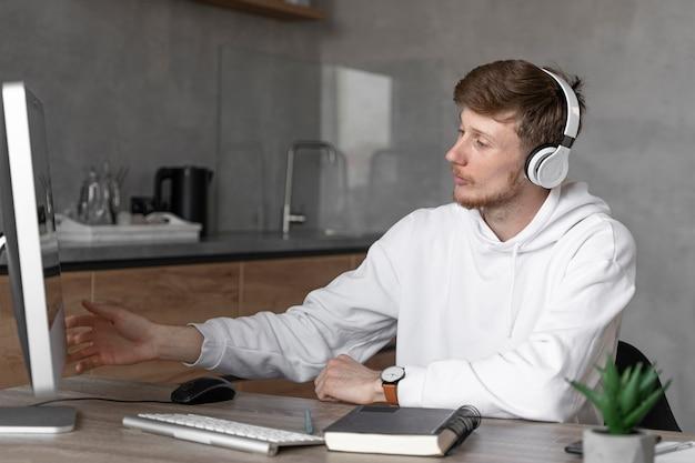 コンピューターとヘッドフォンでメディア分野で働く男の側面図