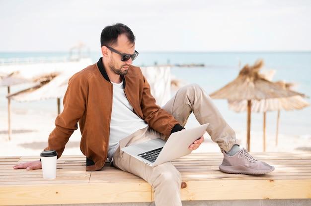 Вид сбоку человека, работающего на ноутбуке на пляже