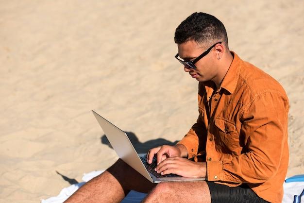 ビーチでラップトップに取り組んでいる男の側面図