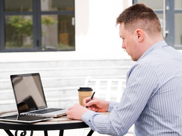 屋外のラップトップで作業する人の側面図