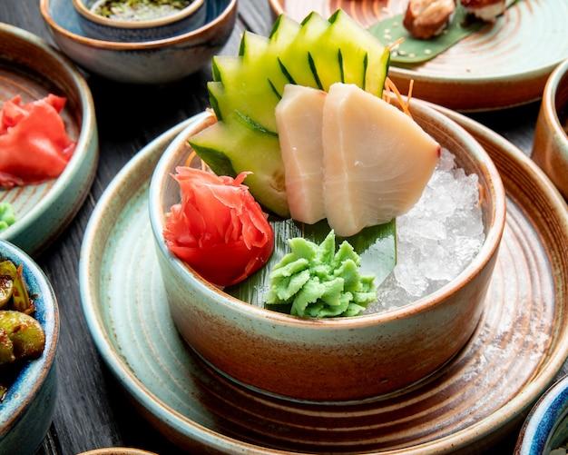 Вид сбоку филе маринованной сельди с ломтиками огурцов, имбирем и соусом васаби на кубиках льда в тарелке на столе