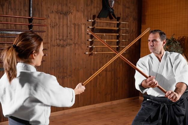 若い女性の研修生と一緒に練習場で武道インストラクターのトレーニングの側面図