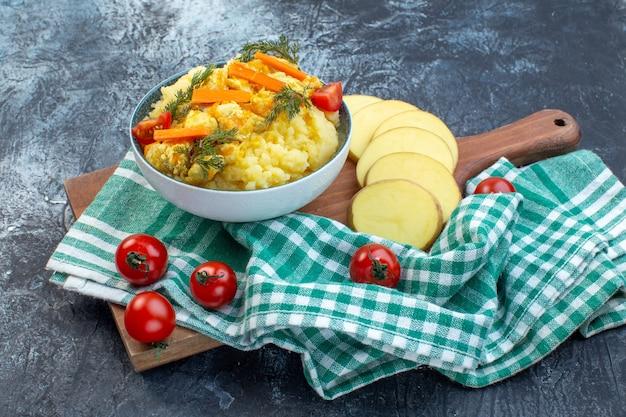 Картофельное пюре с укропом и свежими овощами на зеленом полосатом полотенце на деревянной доске на темном фоне, вид сбоку