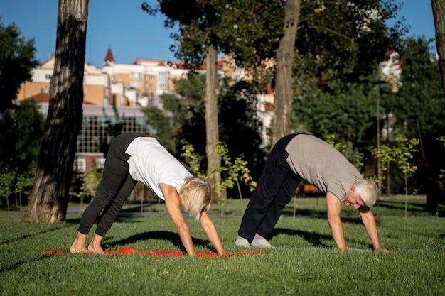Вид сбоку зрелой пары, практикующей йогу на открытом воздухе