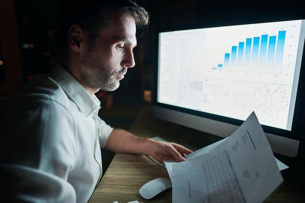 Вид сбоку зрелого мужчины, анализирующего документы в ночное время