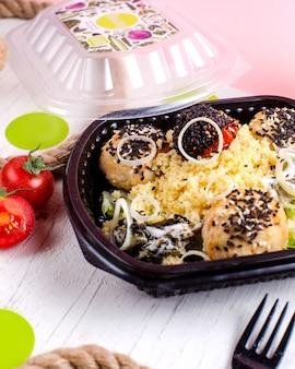 Вид сбоку мясных шариков с пшенной кашей из помидоров и лука в коробке