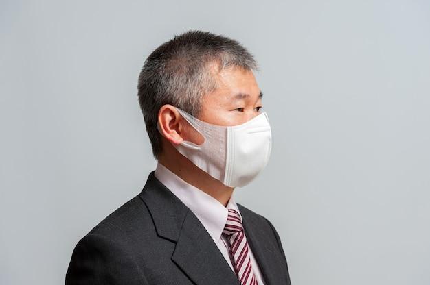 白いサージカルマスクを身に着けているスーツとネクタイと中年のアジア人男性の側面図