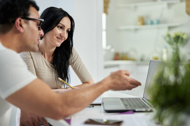 중년 라틴 커플, 남자와 여자가 집에서 노트북을 사용하여 원격으로 공부하는 동안 온라인 교육 과정에서 의사 소통하는 측면보기. 성인을 위한 원격 교육
