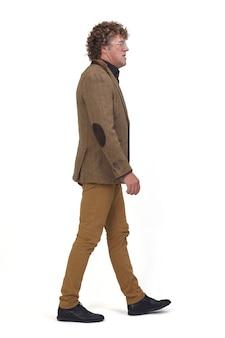 白いスペースを歩いているブレザーを持つ中年男性の側面図、