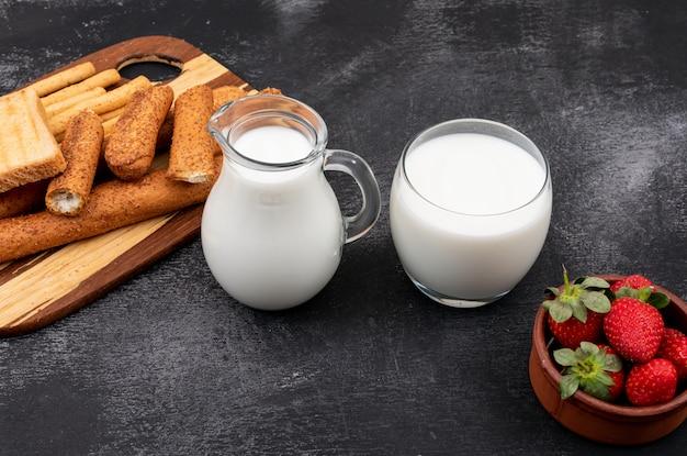 Вид сбоку молока с крекерами и клубникой на черной горизонтальной поверхности