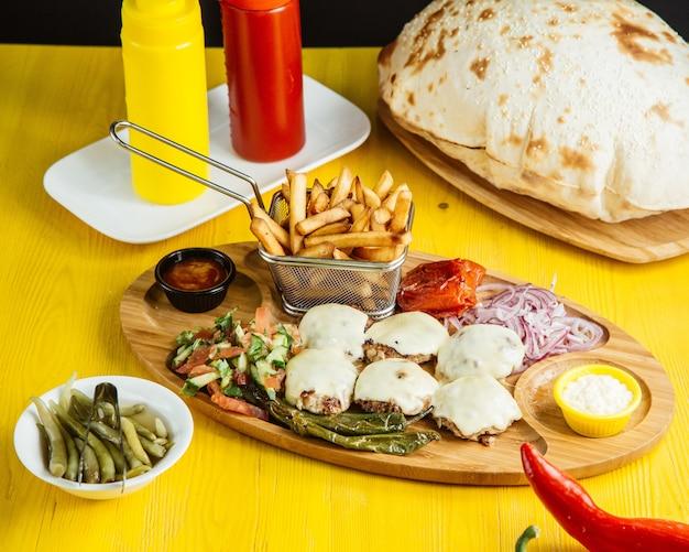溶けたチーズのみじん切り野菜サラダのピクルスとソースの木製大皿とミニカツの側面図