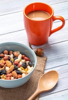 Вид сбоку смеси орехов и сухофруктов в миску и кружку напитка какао на деревенском