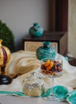 Вид сбоку на смесь орехов и сухофруктов в стеклянной вазе на столе
