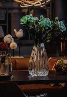 Вид сбоку современной рельефной стеклянной вазе с зелеными цветами на деревянном столе