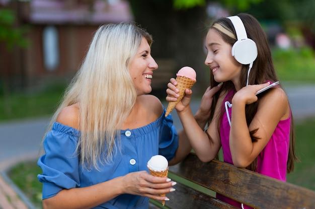 Вид сбоку мамы и дочери в парке
