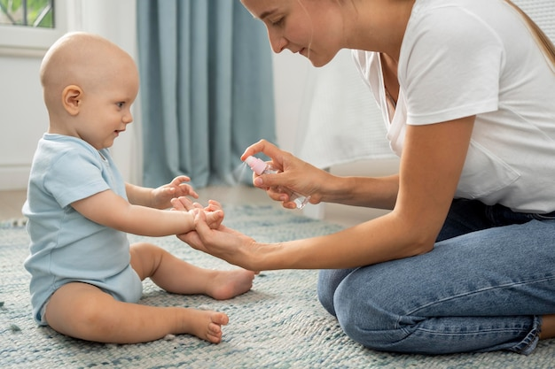 Мама, распыляющая дезинфицирующее средство для рук на руки ребенка, вид сбоку