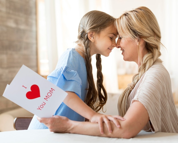 Мать и дочь, вид сбоку, демонстрируют свою любовь друг к другу