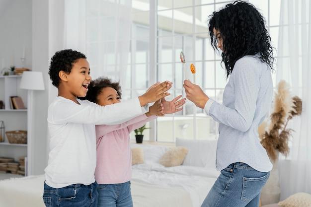 Мать дает своим детям леденцы на палочке, вид сбоку