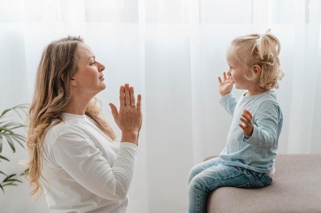 自宅で子供と一緒に祈る母親の側面図